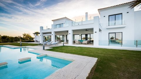 Your La Reserva de Sotogrande villa is a picturesque escape, with gleaming white stucco, set against a clear blue sky and the ocean in the distance. and#13;and#13;The Spanish-style courtyard entry followed by a two-story foyer reveals a modern proper...