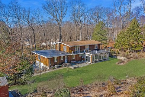 PREPARE TO BE WOWED ...This STUNNING center hall colonial w/a Mid-century contemporary flair, sits on a very private and beautifully landscaped 1.25 acre lot on a cul-de-sac...where redwood joins stone. The two large doors welcome you inside the cust...